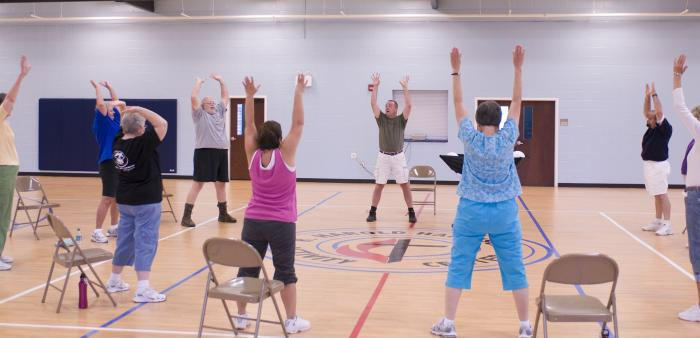 The older individuals pictured here on the wooden floor of an indoor basketball court, were participating in an exercise class consisting of stretching, and aerobic repetitive motion movements. In this particular view, the group members were stretching their torso muscles, and working the muscles of their shoulders by raising their outstretched arms over their head.